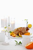 Roast chicken with lemons and oranges on a laid table