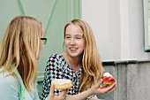Two blonde girls holding cakes
