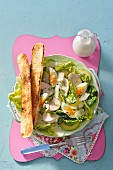 A Chicken Caesar salad served with crostini