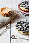 Blackberry tartlets with confectioner's cream and icing sugar