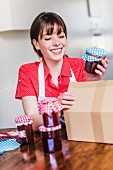 A smiling young woman packing jars of homemade strawberry jam into a box