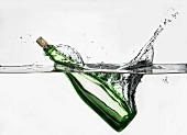 A green corked bottle falling with a splash into water
