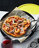 Sliced seafood pizza with white anchovies, prawns, olive oil and dill