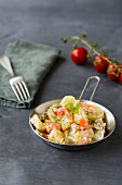 Potato salad with peppers, tomatoes, gherkins and parsley