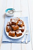 Carrot cake with icing sugar, sliced