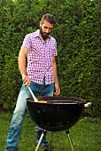 A young man barbecuing salmon trout fillet in a garden