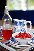 Bowl of fresh wild strawberries on stacked plates and blue and white jug next to vintage bottle in background