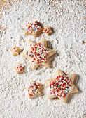 Star biscuits with coloured sprinkles on a sugared wooden board
