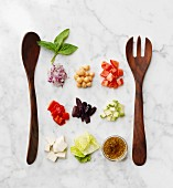 Chopped salad ingredients with salad servers on a marble surface