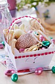 Easter sweets in paper basket decorated with floral ribbonr