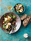 A mixed salad with boiled eggs, beans and rye bread