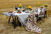Table set with white linen table cloth and yellow sunflowers in stubbly field