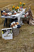 Table set with sunflowers and white linen tablecloth in stubbly field