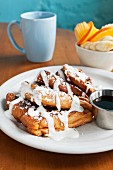 French toast with icing sugar and cream served with syrup, oranges, bananas and coffee