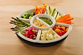 Hummus and pesto dip with raw vegetables in bowls
