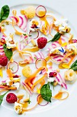 Vegetable salad with edible flowers, cream cheese and raspberries
