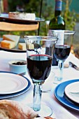 A table laid with glasses of red wine and a stand of cheese in the background