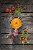 Pumpkin soup in a saucepan on a wooden surface with autumnal decorations