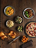 A buffet featuring roast chicken legs, pizza, Irish stew, chicken curry, vegetables, salad, Pad Thai and chips