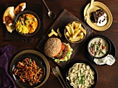 A buffet with hamburger, chips, noodle dishes, beef dishes, green Thai chicken curry, Indian chicken curry and brownies
