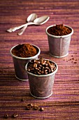 Various types of coffee: coffee beans and powder in metal cups