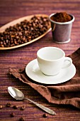 Coffee beans, coffee powder, a coffee cup and a coffee spoon