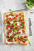 Puff pastry cake with herb cream, tomatoes, rocket and Parmesan