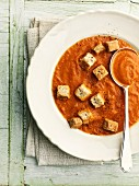 A bowl of tomato soup with croutons and a spoon