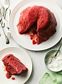 Berry pudding, sliced, with a piece on a plate and a bowl of whipped cream