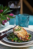 A pork chop on a bed of kale