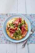 Pizza with ham, rocket, tomatoes and pine nuts