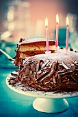 Chocolate cake with grated chocolate, icing sugar and candles on a cake stand