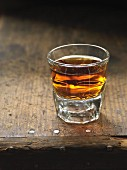 A glass of whisky on a wooden table