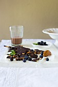 Broken dark chocolate with salted caramel, fresh blueberries and a glass of chocolate milk