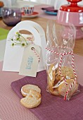 Lemon biscuits in a cellophane bag with a ribbon on a purple place mat
