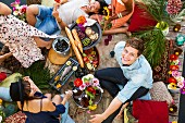 Overhead view of group of friends picnicking on raft
