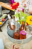 Tray of wine bottles and a vase of flowers on a picnic blanket