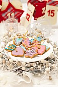Gingerbread biscuits decorated with pastel coloured icing and sugar pearls