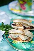 Two pulled pork pitas with vegetable cream on a colourful plate