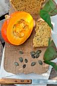 Pumpkin bread with pumpkin seeds and a Hokkaido pumpkin on a chopping board