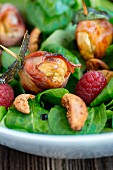 Lamb's lettuce with chestnuts wrapped in bacon, amarettini and raspberries (close-up)
