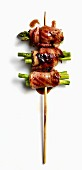 An asparagus and bacon skewer with black pepper teriyaki sauce