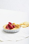 Unbaked shortcrust pastry in a tartlet dish with fresh raspberries