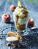 Dessert with fresh peaches, macaroons and cream