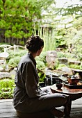 A woman sitting cross-legged at a small tea table in a zen garden
