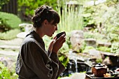 A woman in a zen garden drinking from a tea bowl