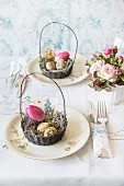 An Easter table decorated with bouquets and an Easter basket filled with eggs and a tulip