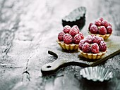 Three raspberry tartlets on a wooden board with tartlet tins