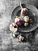 Fresh garlic bulbs and oriental garlic, whole and sliced on and next to a grey plate
