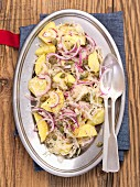 Potato and sauerkraut salad with red onions and capers